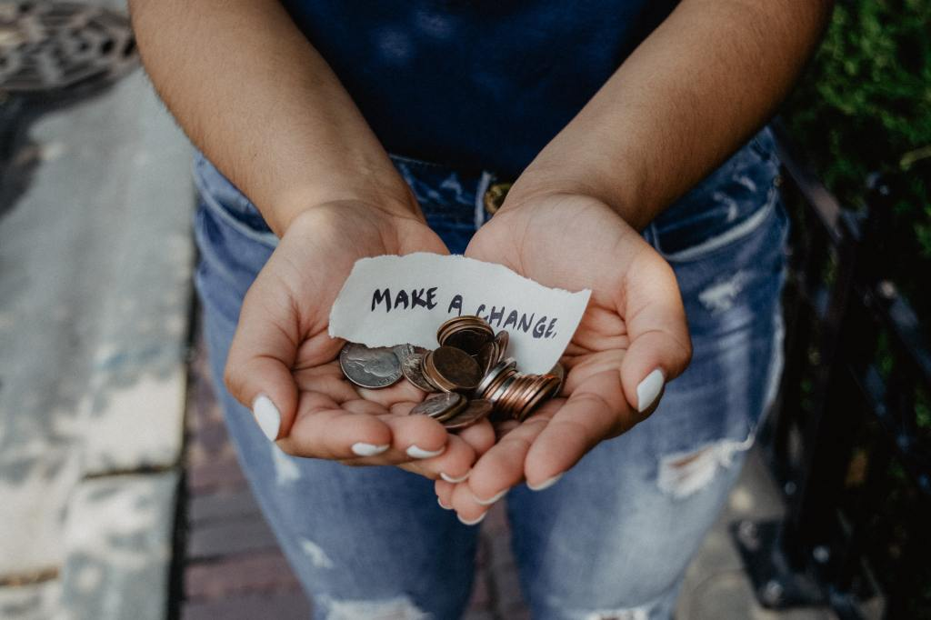 Girl holding change with sign to make a change