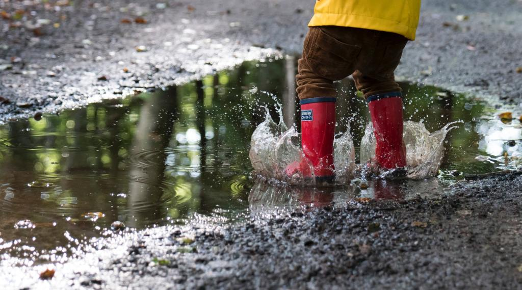 kid playing in a puddle